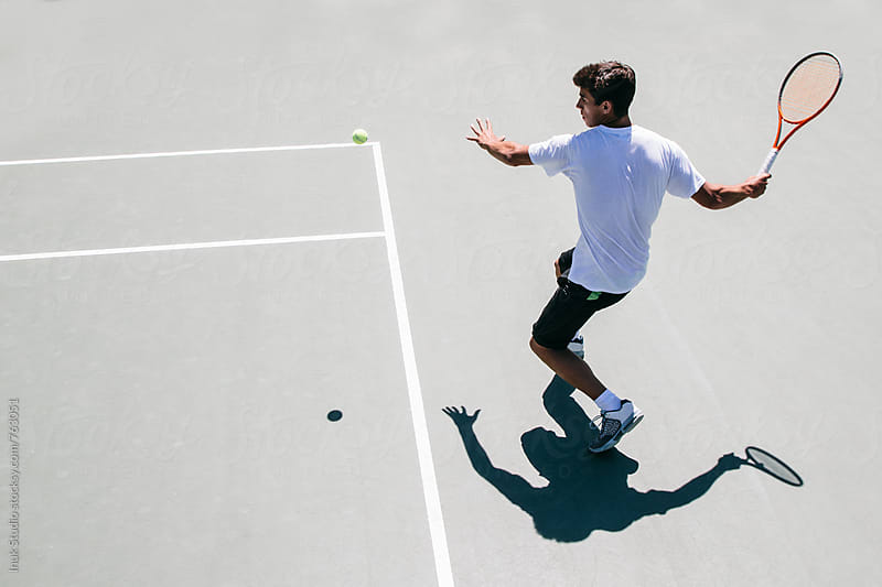 Tennis player moments before hitting the ball in a tennis court seen from above by Inuk Studio for Stocksy United