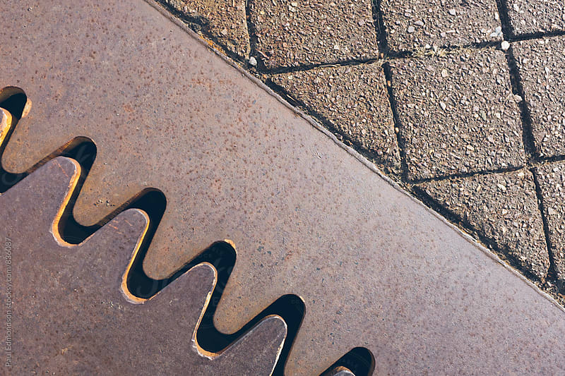 Detail of joined metal plates on urban sidewalk by Paul Edmondson for Stocksy United