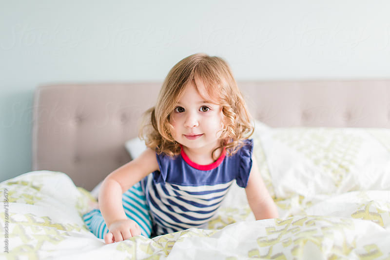 Young toddler girl playing on a bed by Jakob for Stocksy United