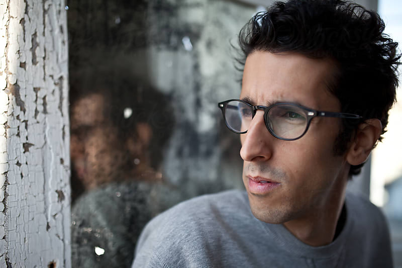 young man with dark hair and glasses with reflection in mirror by Lisa MacIntosh for Stocksy United
