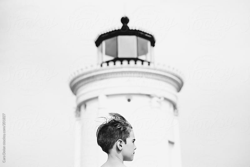 Boy stands in front of lighthouse on a windy day by Cara Dolan for Stocksy United