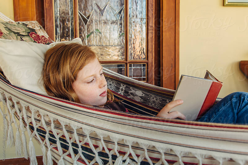 Red hair girl reading a book by Gabriel (Gabi) Bucataru for Stocksy United