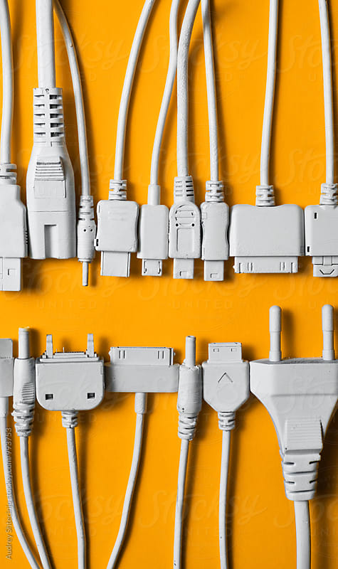 Various cable jacks and plugs on orange background by Audrey Shtecinjo for Stocksy United