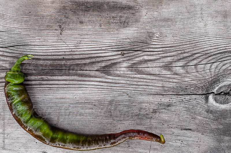 Green and Red Chile Pepper on weathered wood board by Rhonda Adkins for Stocksy United
