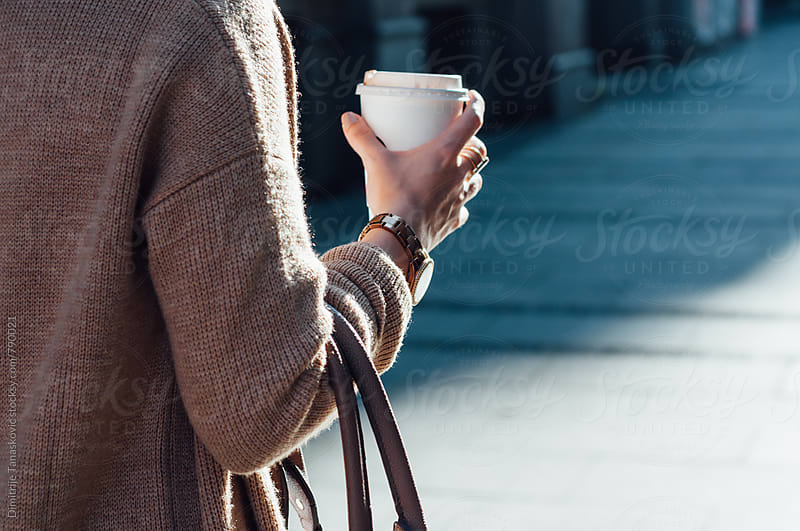 Young Caucasian woman holding cup of coffee. Closeup image. by Dimitrije Tanaskovic for Stocksy United