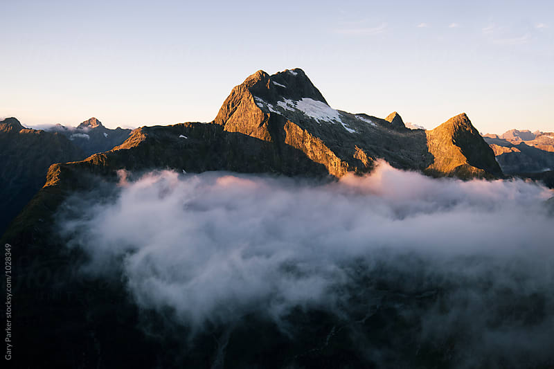 Mountain peak above the clouds by Gary Parker for Stocksy United