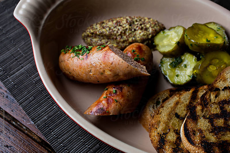 fresh sausage with grilled bread, pickles and mustard by Andrew Cebulka for Stocksy United