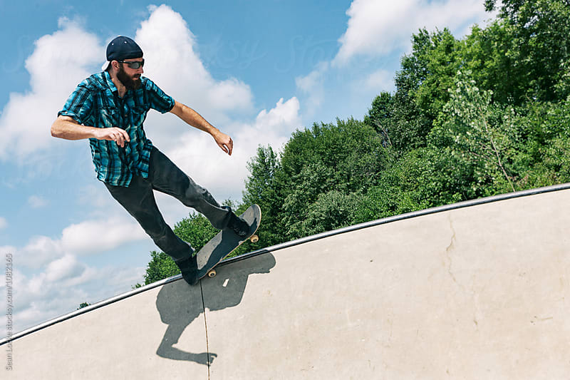 Skateboarder Slides Across Bar At Top Of Wall by Sean Locke for Stocksy United