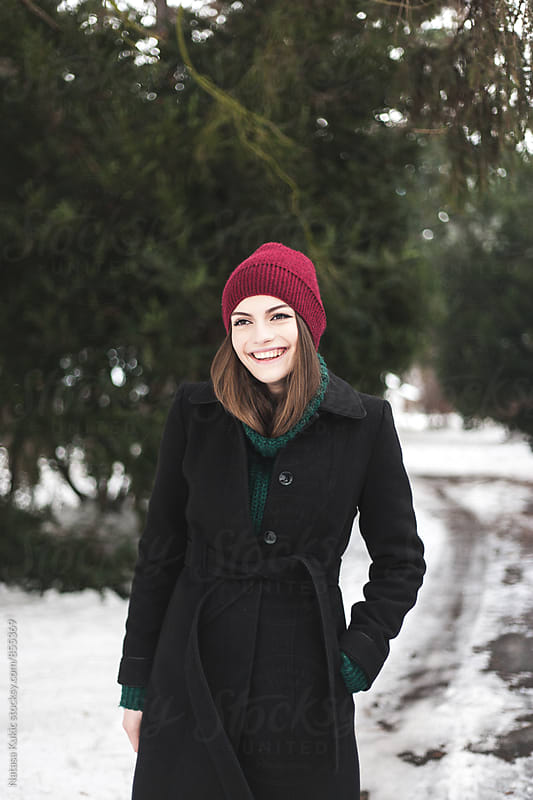 Winter portrait of a beautiful brunette smiling by Natasa Kukic for Stocksy United