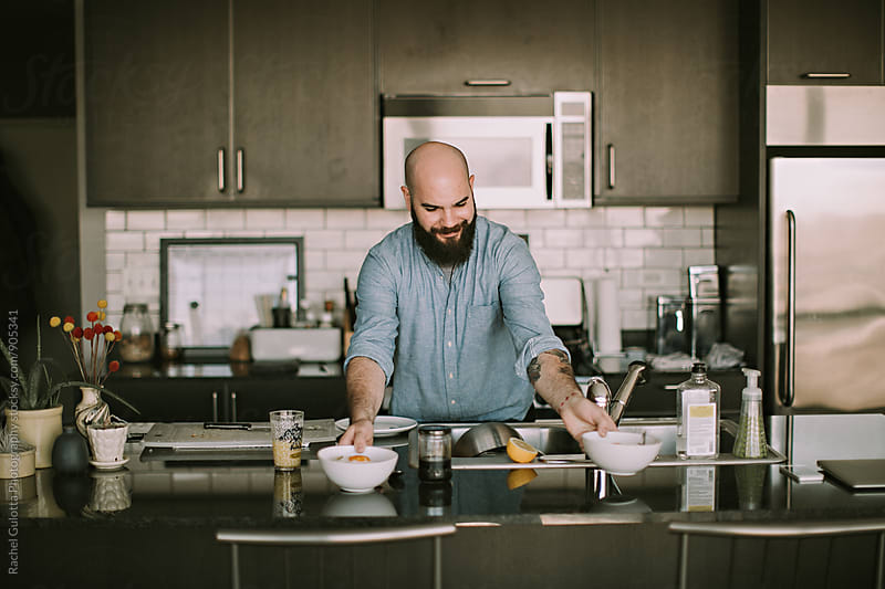 A Young Man Serves Breakfast in His Kitchen by Rachel Gulotta Photography for Stocksy United