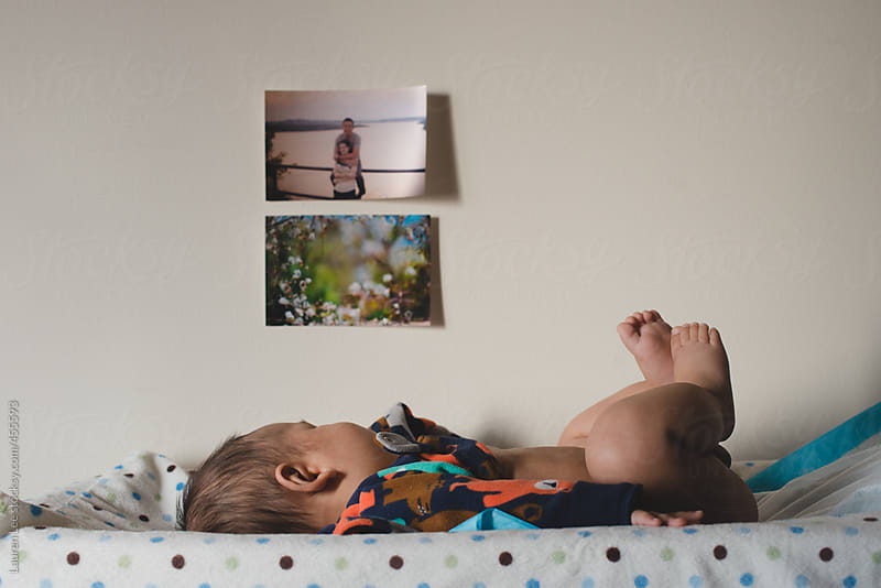 Baby on a changing table looking at photographs by Lauren Naefe for Stocksy United