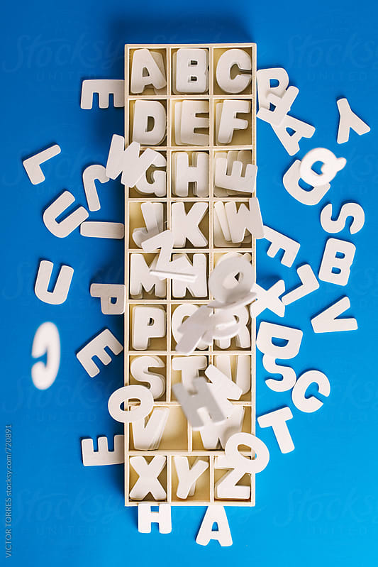 White Letters Falling Inside a Wooden Box by VICTOR TORRES for Stocksy United