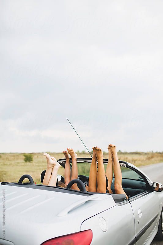 Female friends in cabriolet with legs out by Jovana Rikalo for Stocksy United