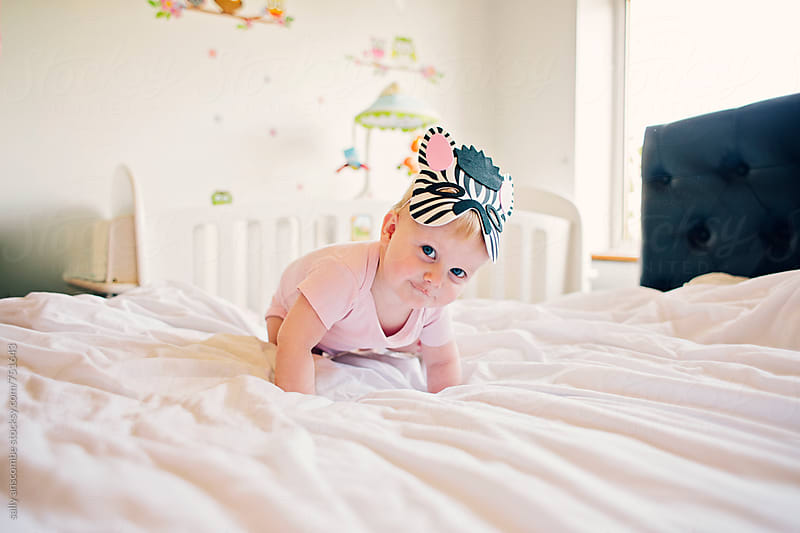 Baby girl wearing a zebra mask by sally anscombe for Stocksy United