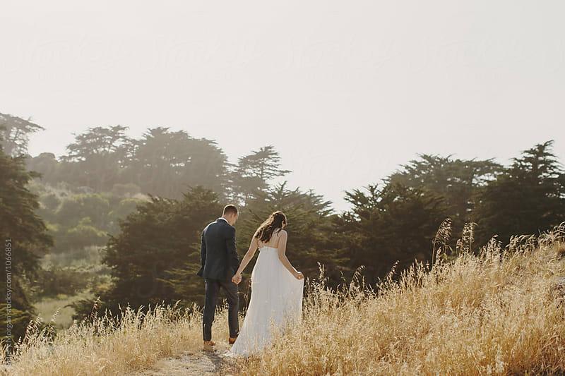 Bride and Groom Walking Away in Field by Sidney Morgan for Stocksy United