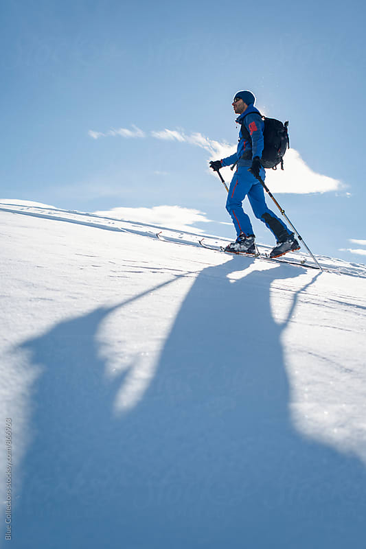 a skier go up the mountain and climbing in a sunny day by Blue Collectors for Stocksy United