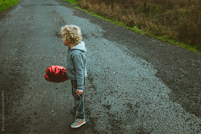 Little Boy Holding Balloon  by Bryan Rupp for Stocksy United