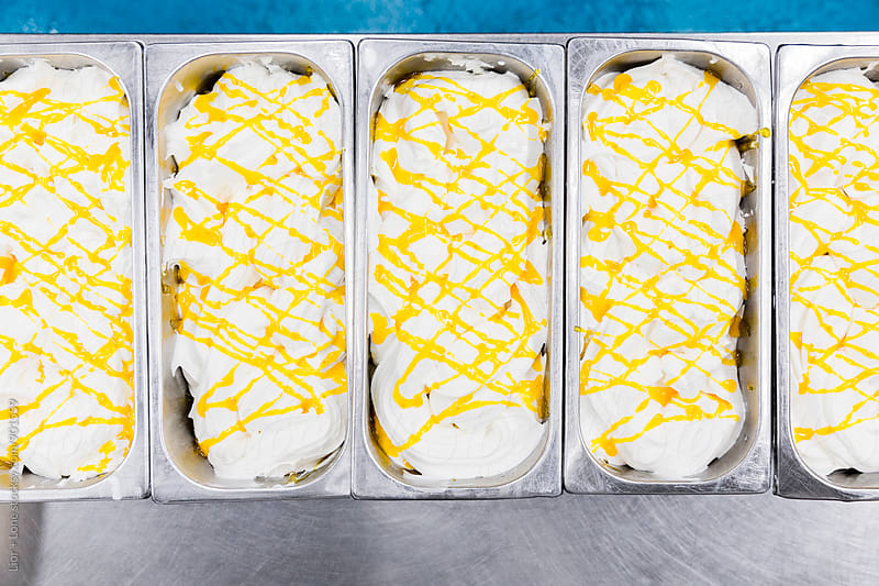 Industrial containers with vanilla ice cream and yellow sauce  by Lior + Lone for Stocksy United