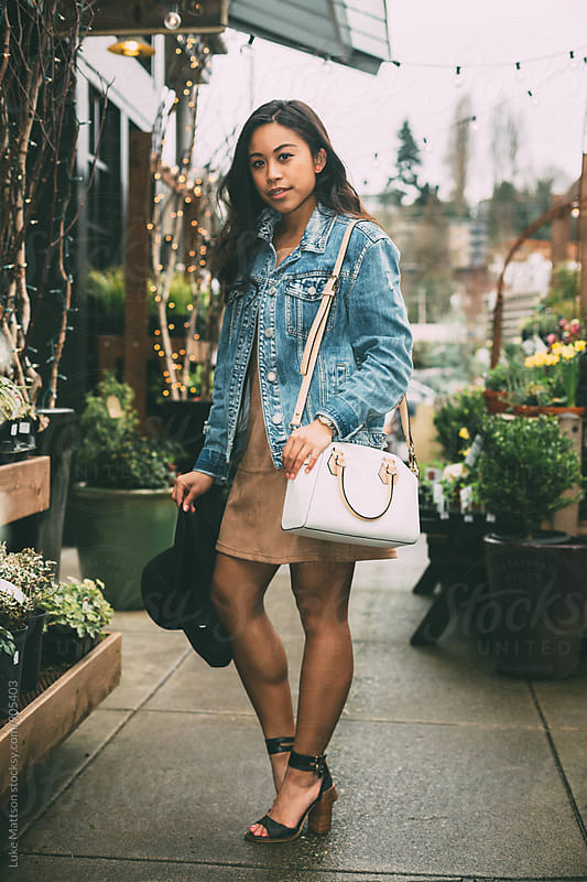 Attractive Young Woman Standing Outside Plant Nursery by Luke Mattson for Stocksy United