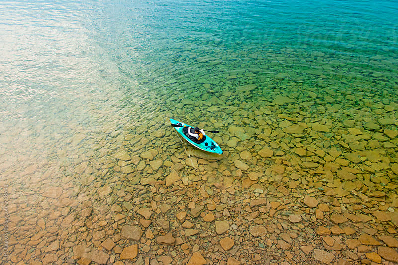 Woman in Sea Kayak Paddling on Crystal Clear Freshwater Lake at Summer Family Cottage by JP Danko for Stocksy United