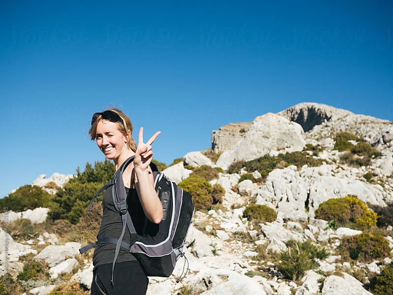 happy hiking Girl doing a V sign under a rock by Martin Matej for Stocksy United
