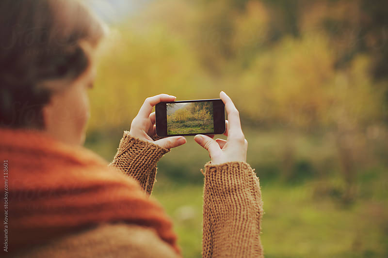 Woman is holding a phone and takes landscape picture by Aleksandra Kovac for Stocksy United