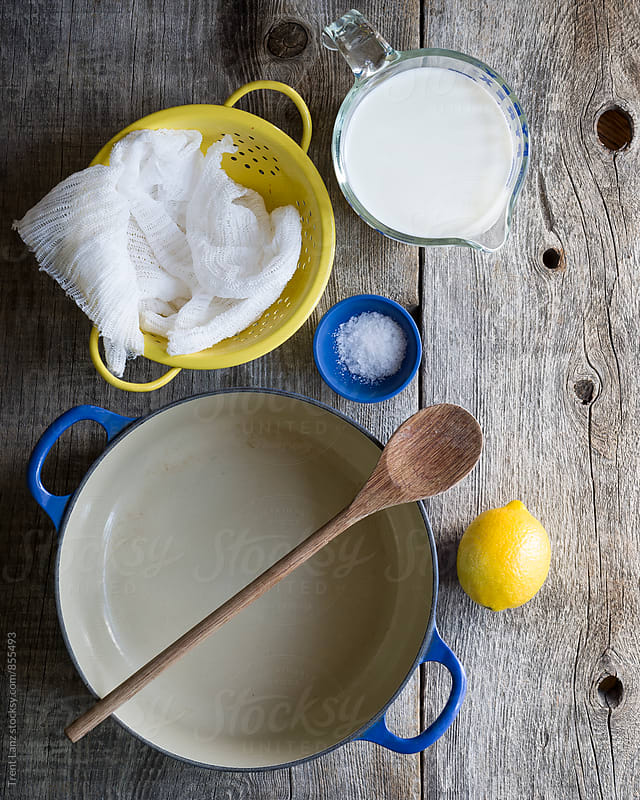 Ingredients on wooden table to make homemade ricotta cheese by Trent Lanz for Stocksy United