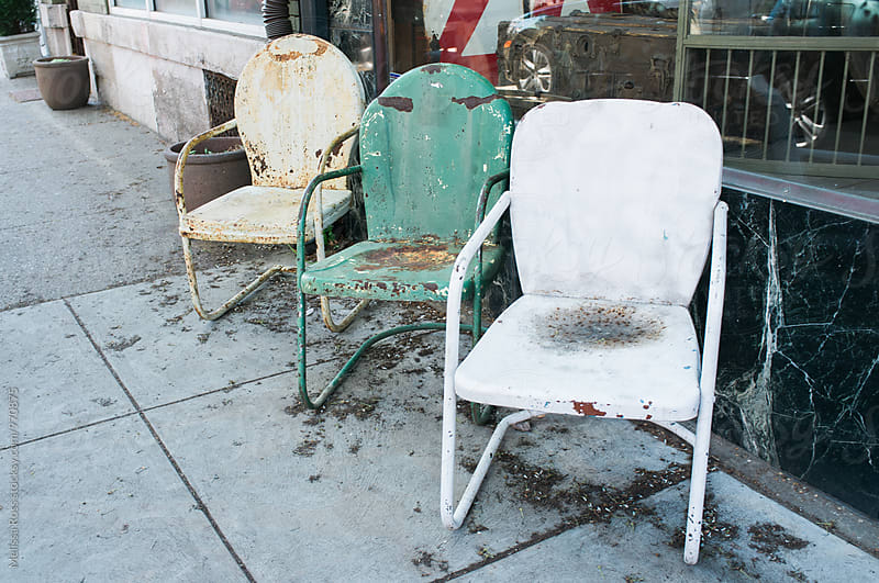 Vintage lawn chairs displayed outside a shop. by Melissa Ross for Stocksy United