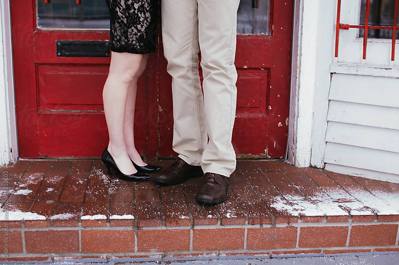 Couple in front of Red Door - Legs by Gabrielle Lutze for Stocksy United