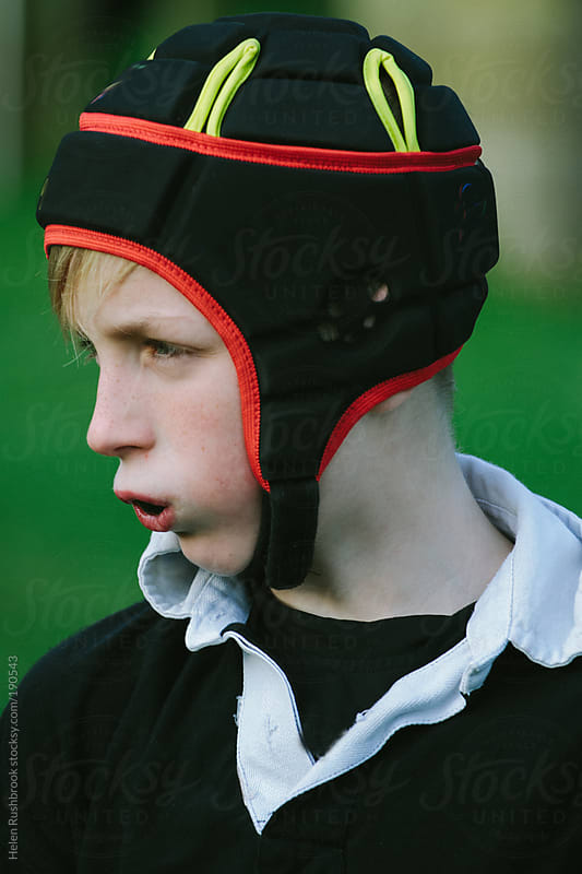 A young boy in rugby kit by Helen Rushbrook for Stocksy United