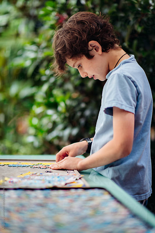 Boy working on a jigsaw puzzle outside by Angela Lumsden for Stocksy United