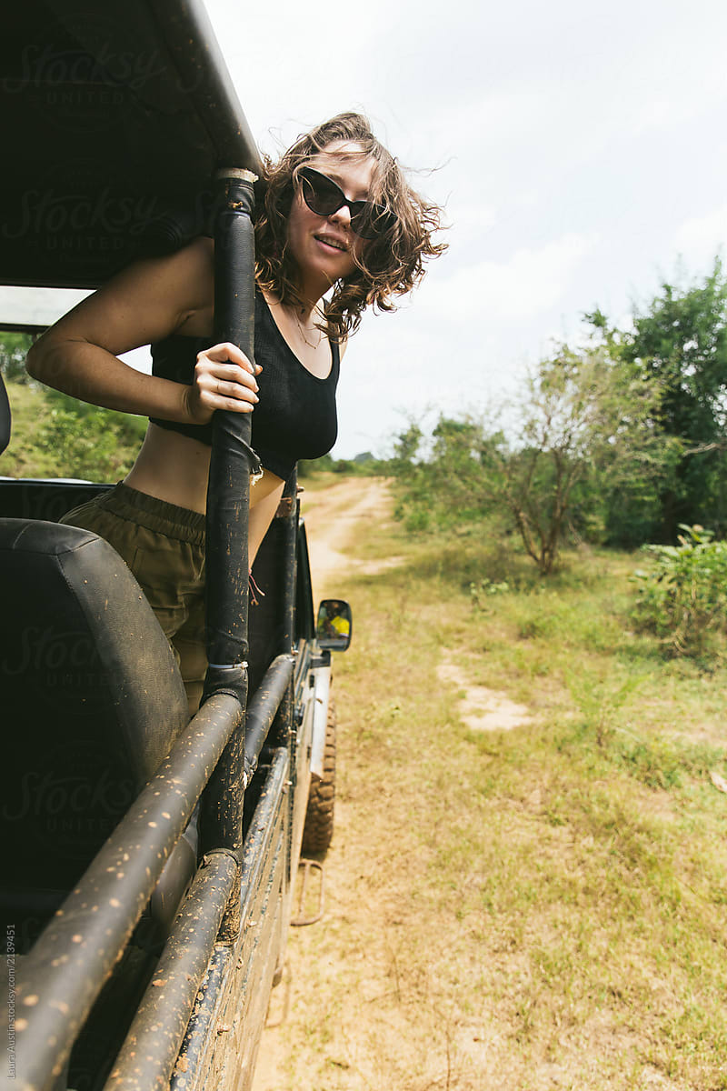 Woman Hanging Out The Side Of A Jeep On Safari Stocksy United