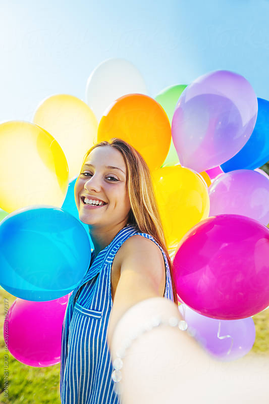 Blonde girl taking a selfie with colorful balloons on a sunny day. by BONNINSTUDIO for Stocksy United