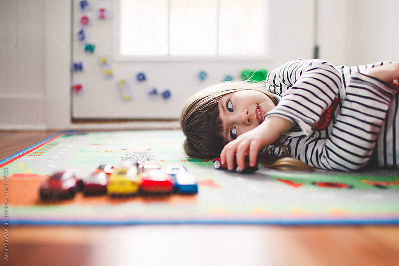 Young girl lays on floor playing with toy cars by Amanda Worrall for Stocksy United