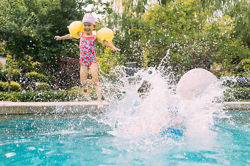 Cute little girl jumping into swimming pool by MaaHoo Studio for Stocksy United