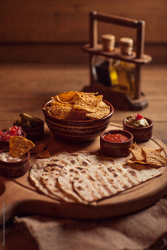 Mexican Nachos Tortilla and Dips served on a wooden plate. by Mosuno for Stocksy United