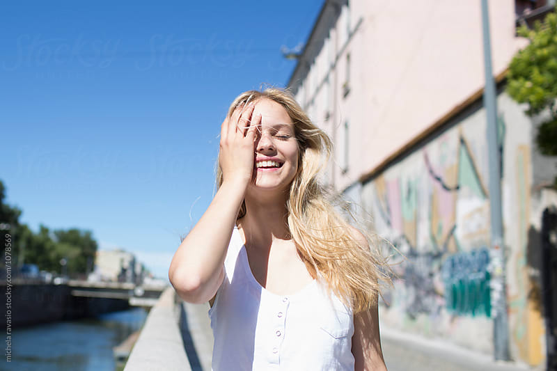 Beautiful girl with long blond hair smiles by michela ravasio for Stocksy United