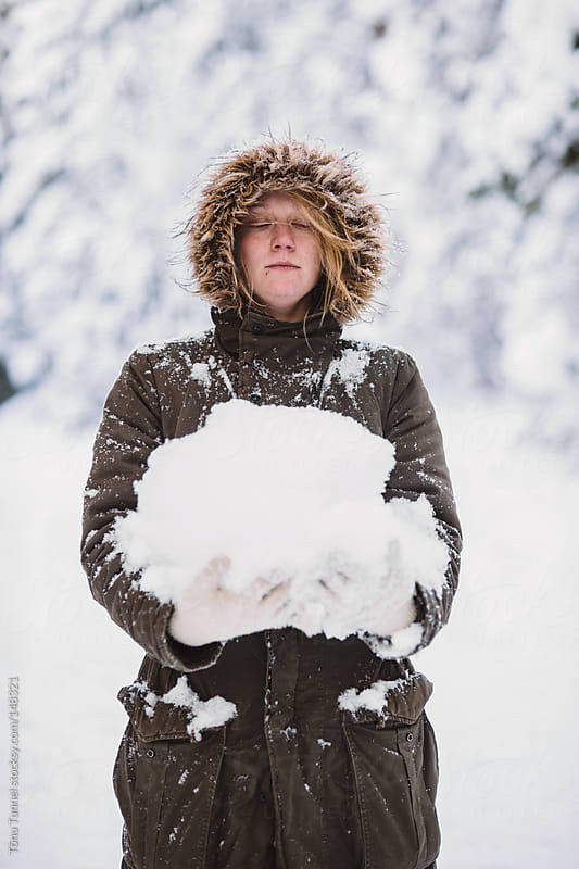 A girl holding a pile of snow by Tõnu Tunnel for Stocksy United