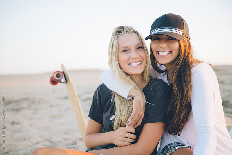 Two SoCal friends hanging out and sitting on the beach.  by Emmanuel Hidalgo for Stocksy United