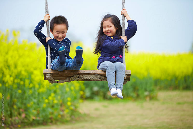happy kids on swing by Bo Bo for Stocksy United