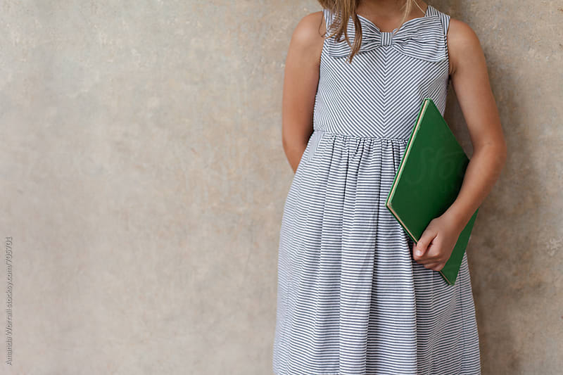Anonymous school girl wearing a striped dress with bow holding a green book by Amanda Worrall for Stocksy United