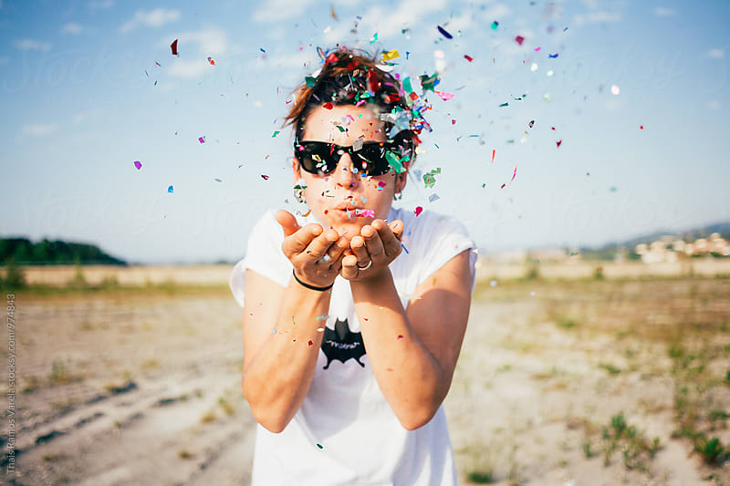 woman blowing confetti by Thais Ramos Varela for Stocksy United