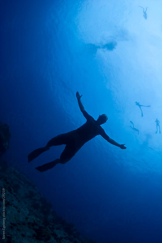 Free diver with open arms on blue water background by Søren Egeberg Photography for Stocksy United