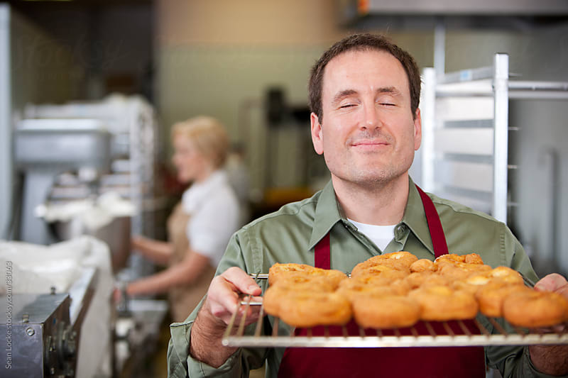 Bakery: Man Loves Smell of New Donuts by Sean Locke for Stocksy United