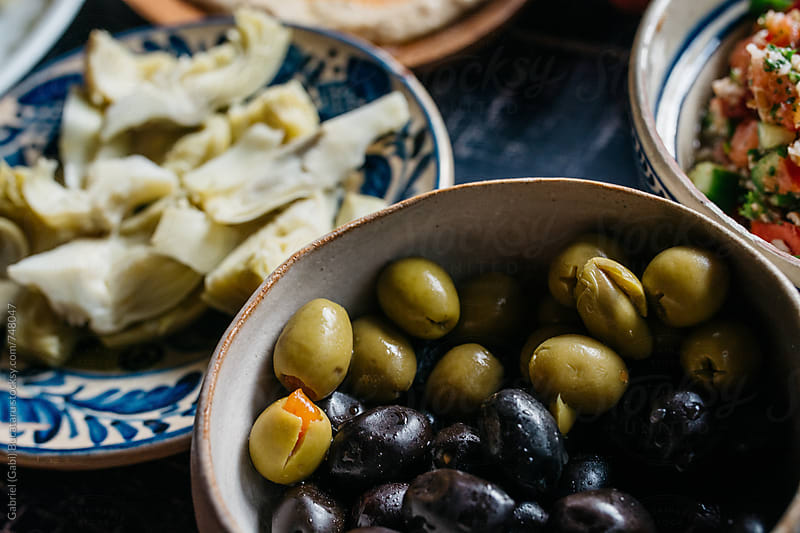 Black and green olives in a bowl by Gabriel (Gabi) Bucataru for Stocksy United