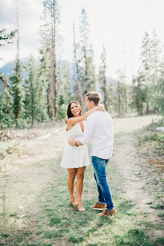 Couple laugh and embrace in forest by Luke Liable for Stocksy United