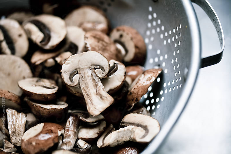 Mushrooms in a colander after they've been washed by Carolyn Lagattuta for Stocksy United