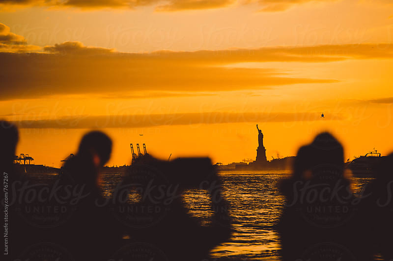 People photographing Statue of Liberty and Manhattan skyline by Lauren Naefe for Stocksy United