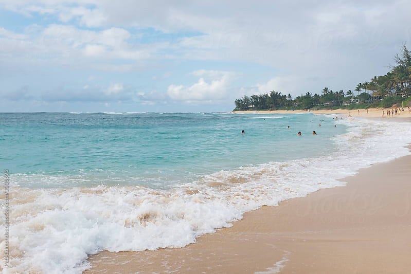 Sunbathers and swimmers at Sunset Beach, North Shore, Oahu, Hawaii by Paul Edmondson for Stocksy United