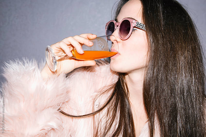 Young woman in pink fur coat drinking orange juice by Danil Nevsky for Stocksy United
